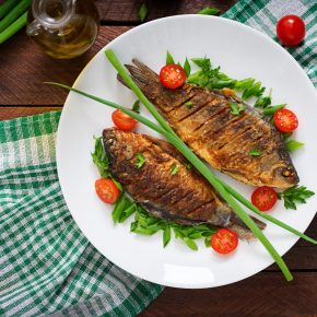 fried-fish-carp-fresh-vegetable-salad-wooden-table-flat-lay-top-view